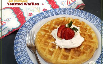 "waffle on a plate topped with strawberry and whipped cream with text overlay ""old fashioned yeasted waffles"""