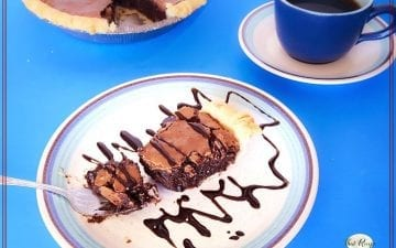"""chocolate pie on a plate with cup of coffee and text overlay """"fudgy brownie pie"""""""