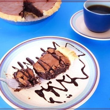 "chocolate pie on a plate with cup of coffee and text overlay ""fudgy brownie pie"""