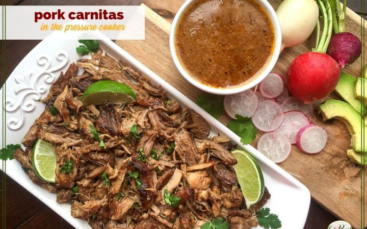 plate of pork carnitas with sauce and vegetables on the side.