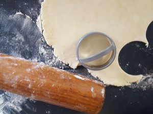 rolled out pastry dough with rolling pin and biscuit cutter