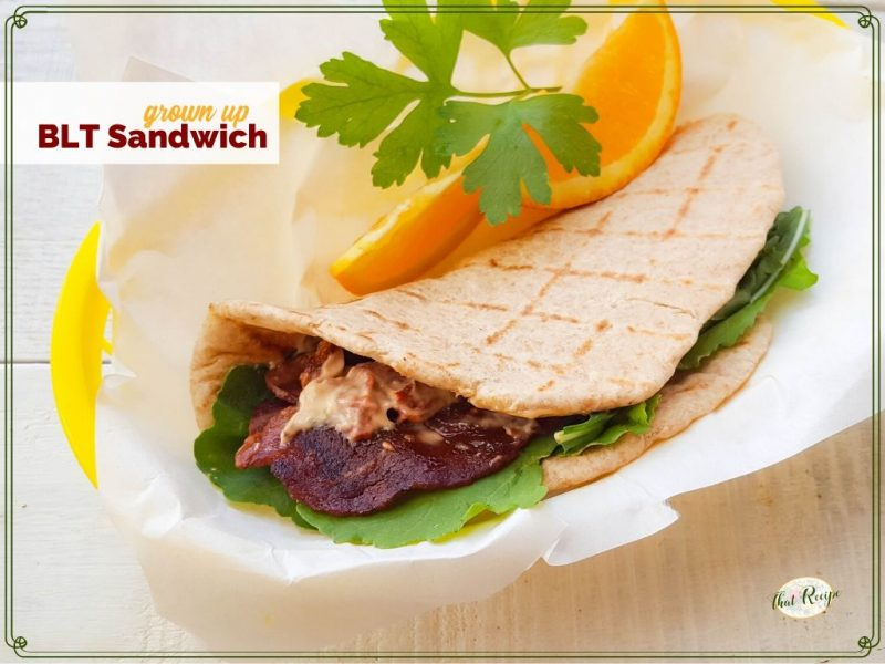 """BLT pita wrap with orange slices and text overlay """"grown Up BLT Sandwich"""""""
