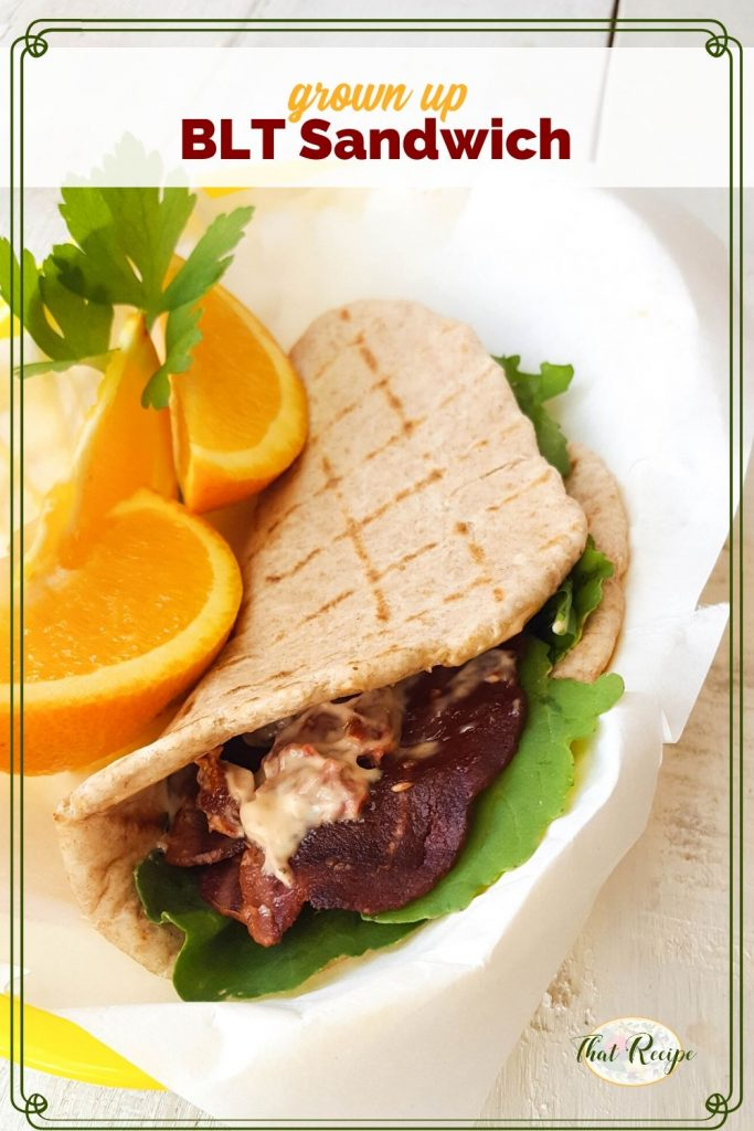 "BLT pita wrap with orange slices and text overlay ""grown Up BLT Sandwich"""