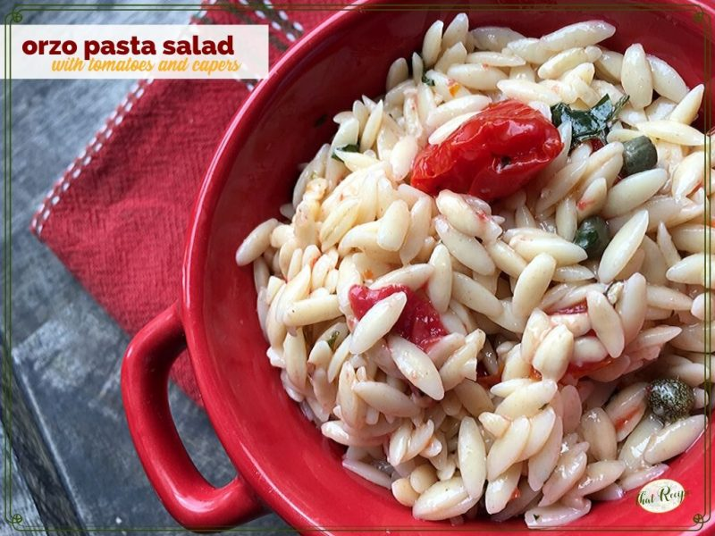 """orzo pasta salad in a red bowl on blue slate with text overlay """"orzo pasta salad with tomatoes and capers"""""""