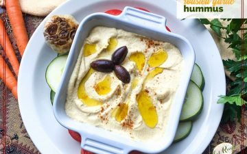 "bowl of hummus with olive oil drizzle and kalamata olives and text overlay ""roasted garlic hummus"""