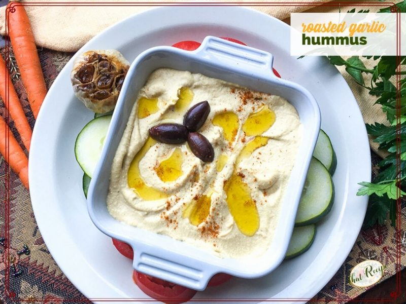 """bowl of hummus with olive oil drizzle and kalamata olives and text overlay """"roasted garlic hummus"""""""