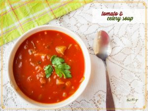 overhead view of tomato and celery soup in a bowl with a spoon