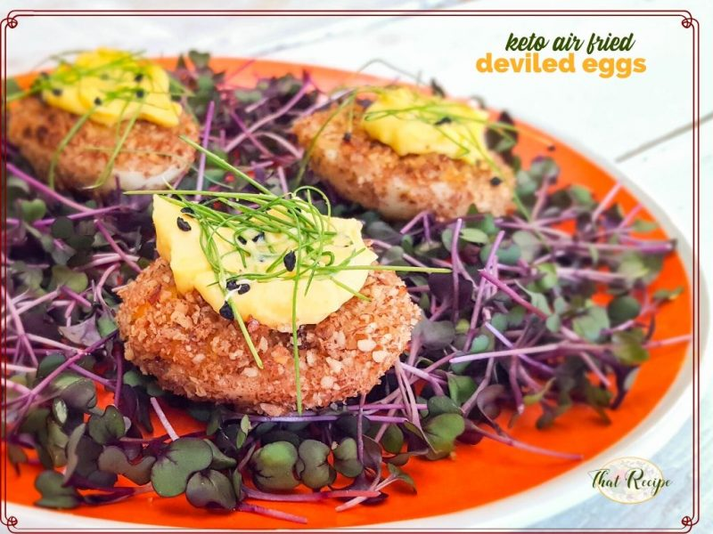 """fried deviled eggs on bed of microgreens with text overlay """"keto air fried deviled eggs"""""""