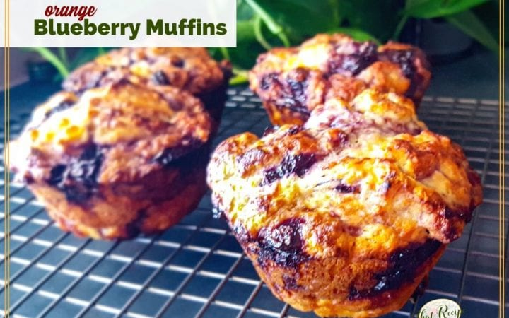 """jumbo muffins on a cooling rack with text overlay """"orange blueberry muffins"""""""