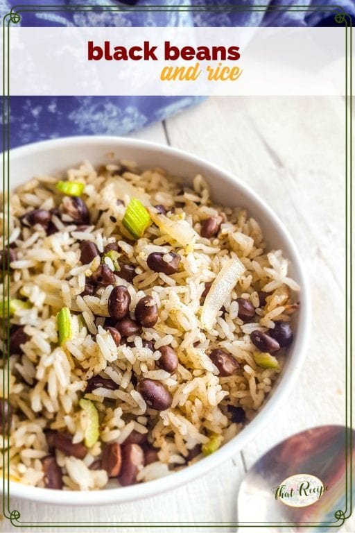 bowl of black beans and rice on white wood background with blue cloth