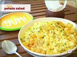 "bowl of potato salad on a picnic table with text overlay ""cajun potato salad"""
