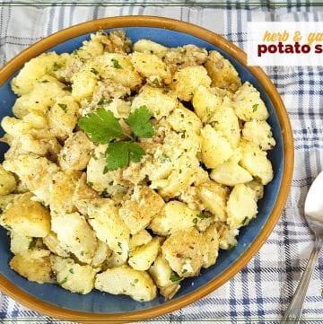 """top down view of potato salad on a picnic blanket with text overlay """"herb and garlic potato salad"""""""