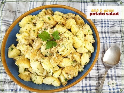 "top down view of potato salad on a picnic blanket with text overlay ""herb and garlic potato salad"""