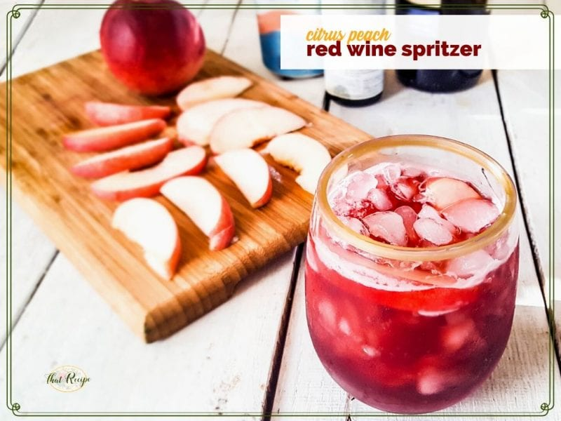 """glass of red wine spritzer with peach slices on a cutting board """"citrus peach red wine spritzer"""""""