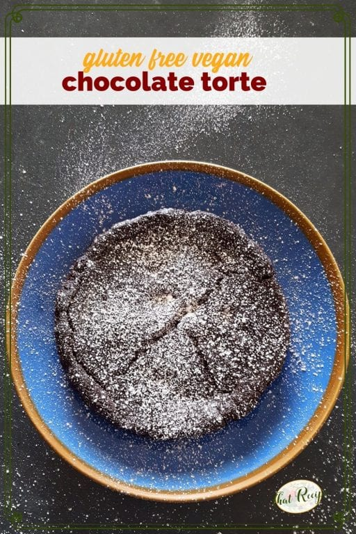"chocolate torte on a blue plate covered in powdered sugar with text ""gluen free vegan chocolate torte"