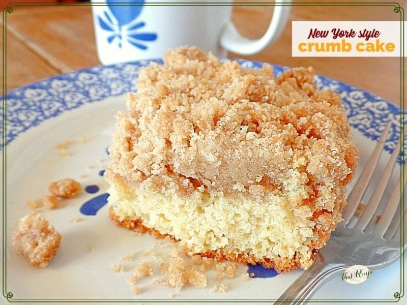 """slice of coffee cake on plate with coffee mug in background and text overlay """"New York style crumb cake"""""""