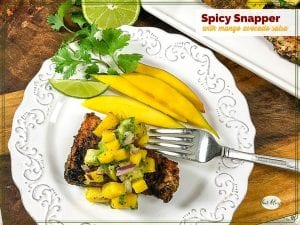 """cajun snapper on a plate topped with mango salsa and text overlay """"spicy snapper with mango avocado salsa"""""""