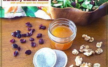 "salad dressing in a jar with cranberries, walnuts, tea bags and a salad bowl around it and text overlay ""cranberry walnut salad with caramel apple tea dressing"""
