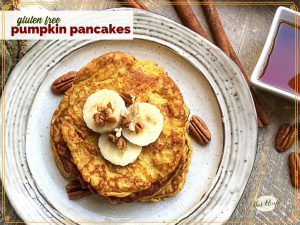 """top down view of pancakes on a plate topped with pecans and banana slices and text overlay """"gluten free pumpkin pancakes"""""""