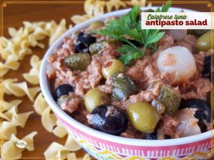 """bowl of antipasto salad on a table surrounded by pasta with text overlay """"Calabrese tuna Antipasto Salad"""""""