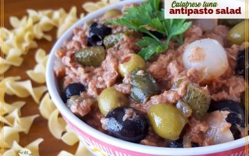 "bowl of antipasto salad on a table surrounded by pasta with text overlay ""Calabrese tuna Antipasto Salad"""
