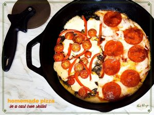 "top down view of cast iron skillet pizza with text overlay ""Homemade pizza in a cast iron skillet"""