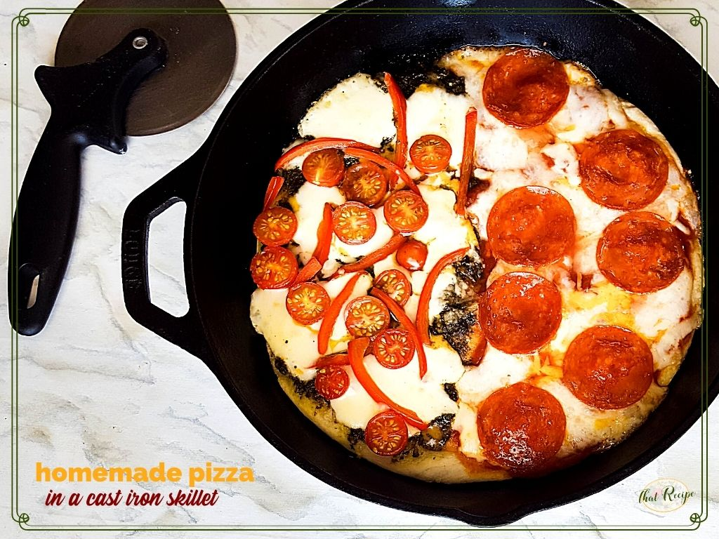 """top down view of cast iron skillet pizza with text overlay """"Homemade pizza in a cast iron skillet"""""""