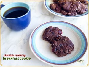 """two chocolate cookies on a plate with a cup of coffee next to it and text overlay """"Chocolate cranberry breakfast cookies"""""""