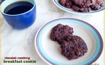 "two chocolate cookies on a plate with a cup of coffee next to it and text overlay ""Chocolate cranberry breakfast cookies"""