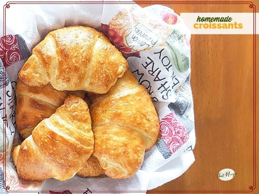 "top down view of croissants in a basket with text overlay ""homemade croissants"""