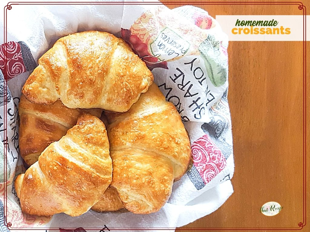 """top down view of croissants in a basket with text overlay """"homemade croissants"""""""