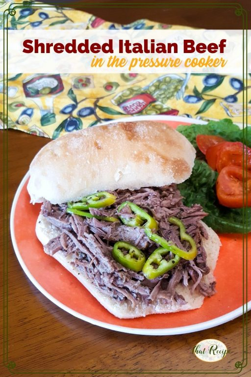 """shredded beef sandwich on a plate with lettuce, tomatoes and peppers with text overlay """"Shredded Italian Beef in the pressure cooker"""""""
