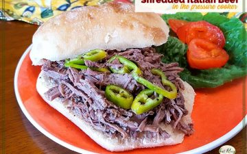 "shredded beef sandwich on a plate with lettuce, tomatoes and peppers with text overlay ""Shredded Italian Beef in the pressure cooker"""