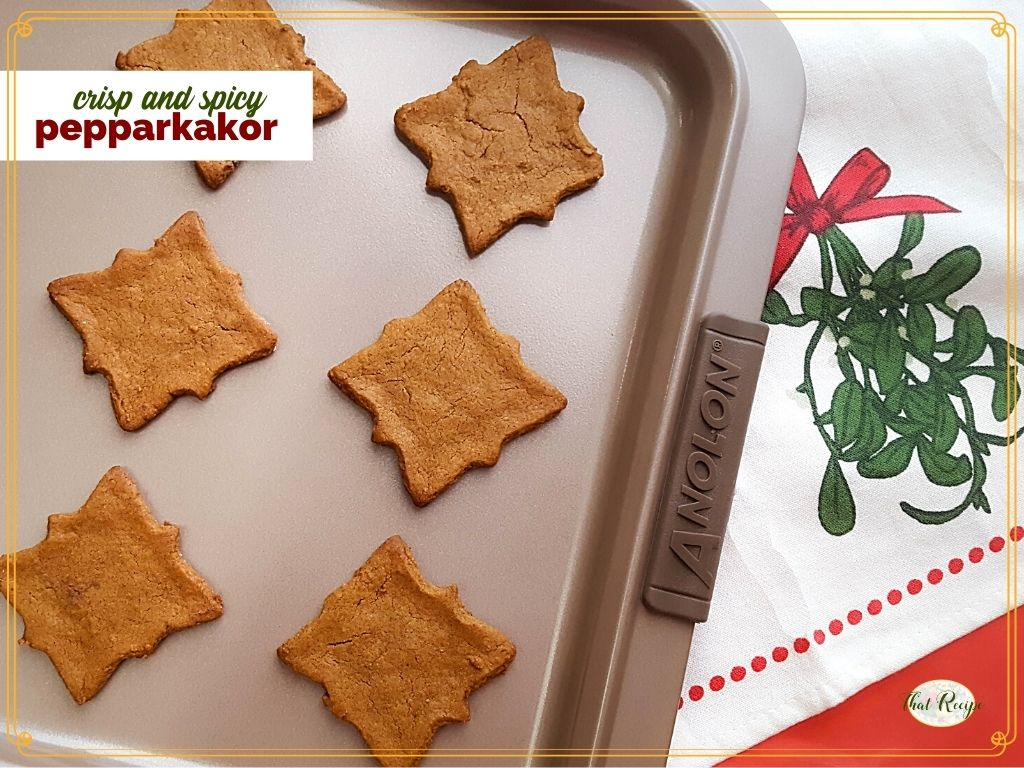 "cut out cookies on a baking tray with text overlay ""sweet and spicy Pepparkakor"""