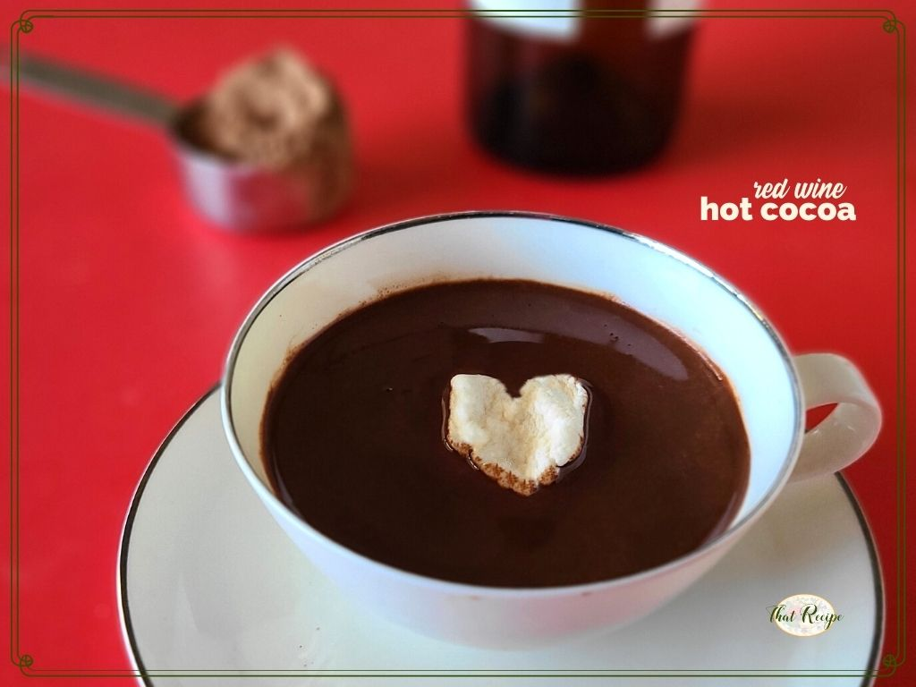 "cup of cocoa with heart shaped marshmallow and text overlay ""red wine hot cocoa"""