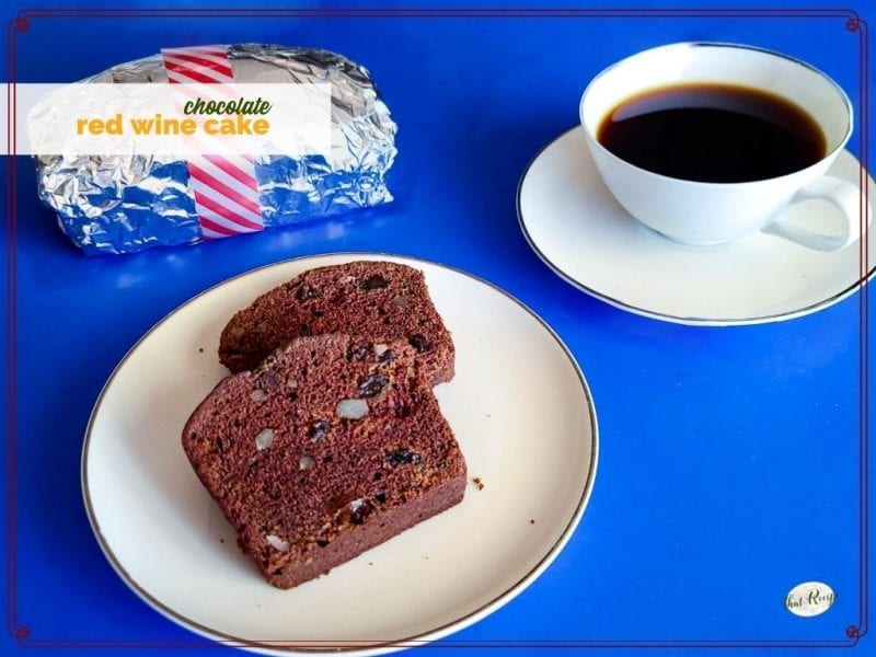 "slices of chocolate loaf cake on a plate with foil wrapped loaf and coffee and text overlay ""chocolate red wine cake"""