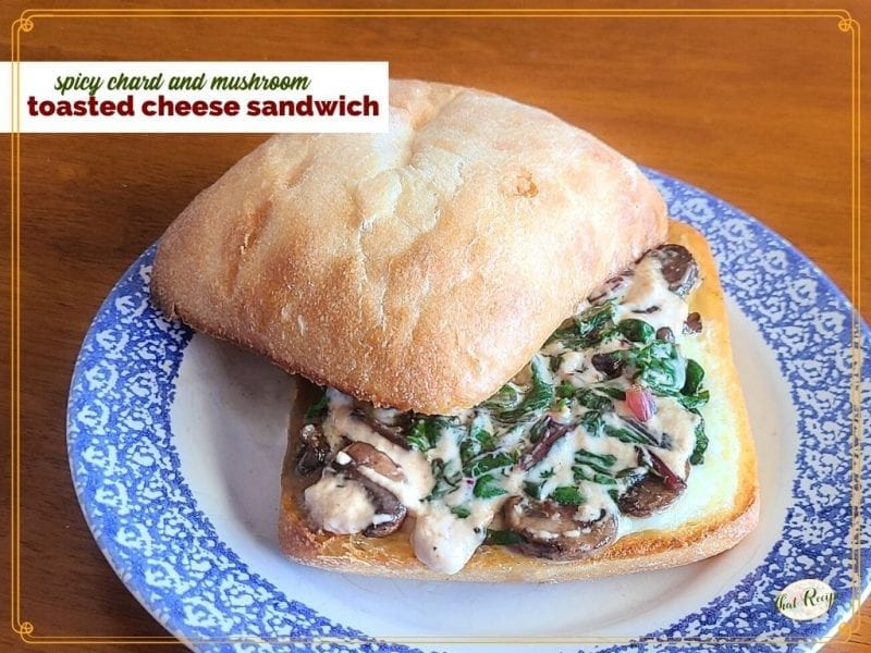 "sandwich on a plate with text overlay ""chard and mushroom toasted cheese sandwich"""