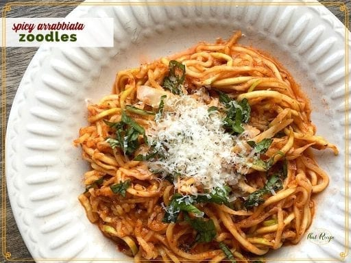 """zucchini noodles with pasta sauce and parmesan on a plate with text overlay """"spicy Arrabbiata Zoodles"""""""