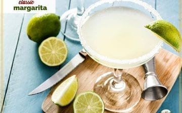 "margarita in a glass surrounded by cut limes with text overlay ""classic margarita"""
