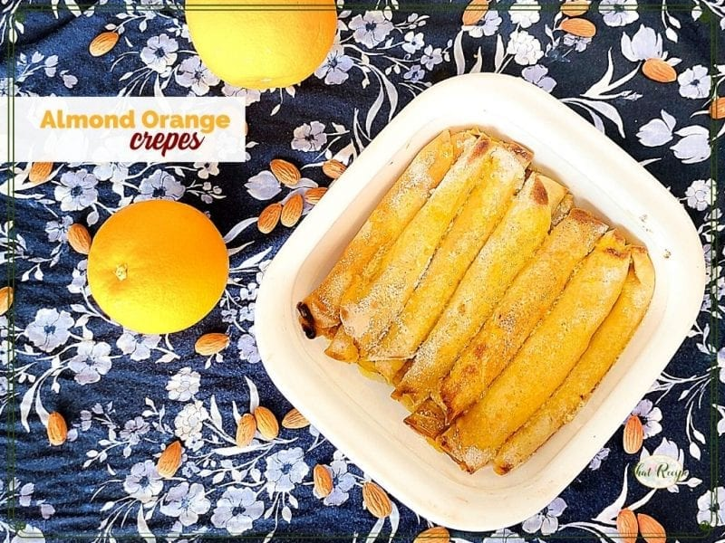 """top down view of crepes in a dish surrounded by oranges and almonds with text overlay """"almond orange crepes"""""""