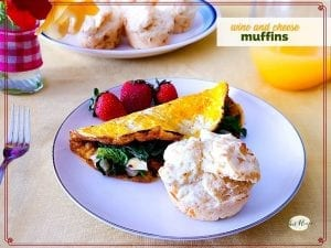 """muffin on a plate with spinach omelet and fresh fruit and text overlay """"wine and cheese muffins"""""""