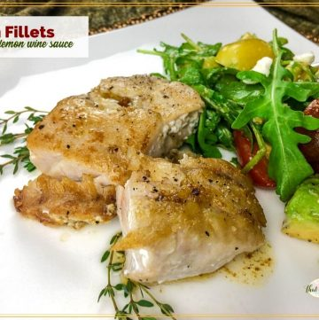 """cooked fish fillet on a plate with text overlay """"fish fillets with lemon wine sauce"""""""