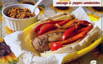"Italian sausage and pepper sandwich on a table with baked beans and text overlay ""grilled sausage and pepper sandwich"""