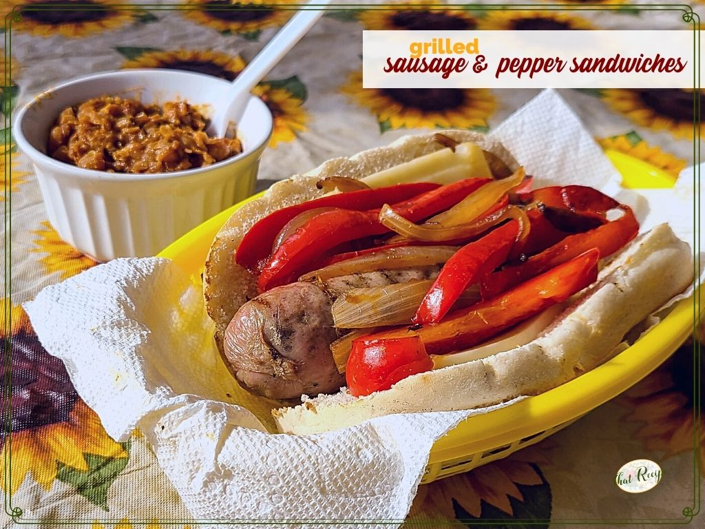 """Italian sausage and pepper sandwich on a table with baked beans and text overlay """"grilled sausage and pepper sandwich"""""""