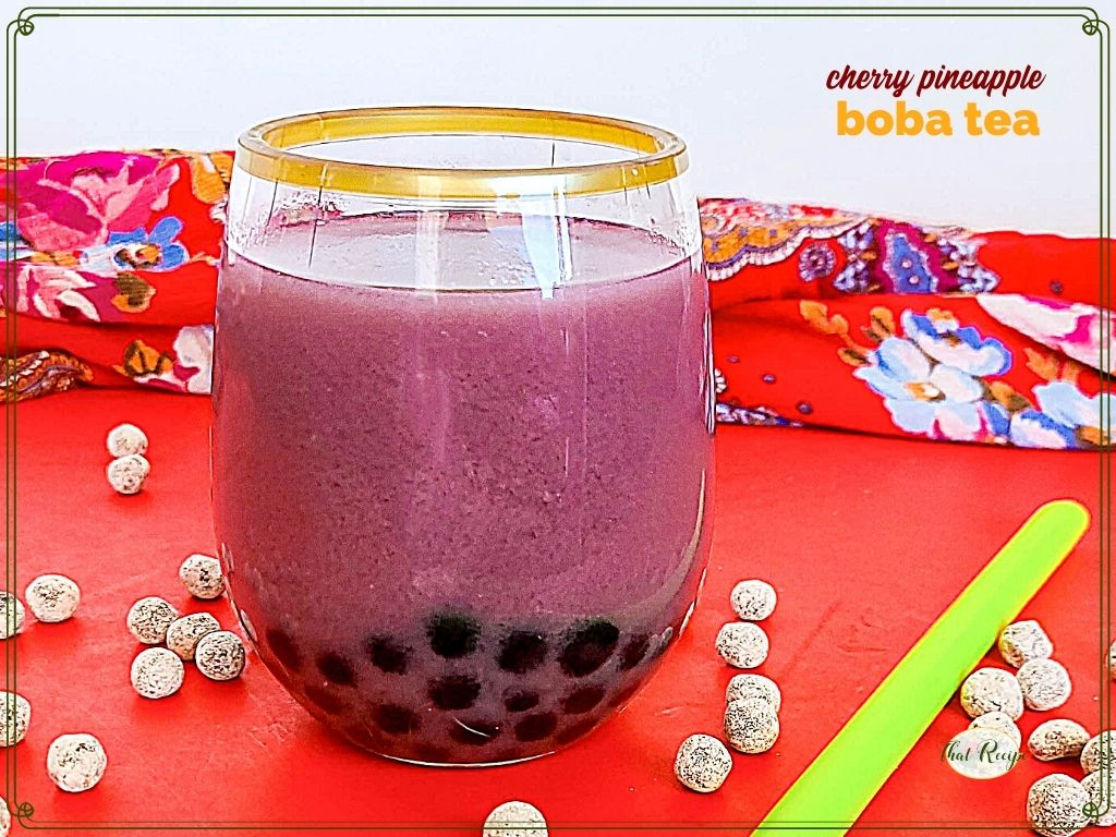 """glass of bubble tea surrounded by uncooked tapioca pearls and text overlay """"cherry pineapple boba tea"""""""