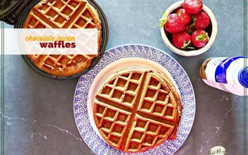 """waffles on a plate and on a waffle iron with strawberries and whipped cream and text overlay """"chocolate pecan waffles"""""""
